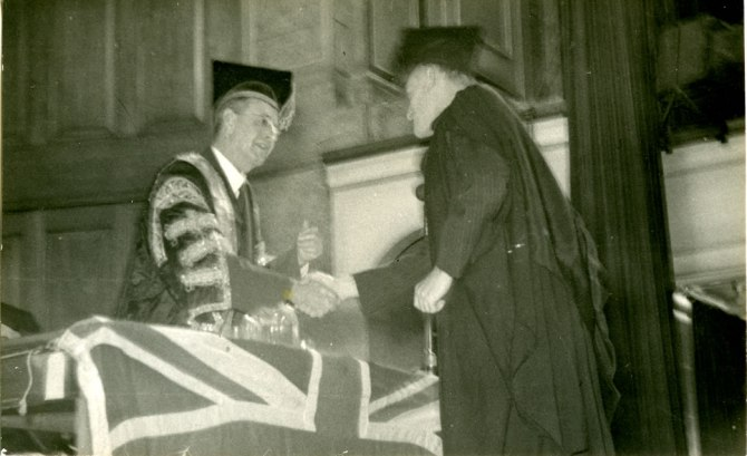 James Carr receiving his degree at the Newcastle Town Hall before the Union Jack