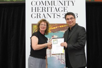 UoN Conservator Amir Mogadam receiving Certificate from National Library representative.