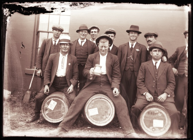 Group of slightly drunk looking men, three sitting on Tooth & Co., Limited Morpeth Beer Barrels