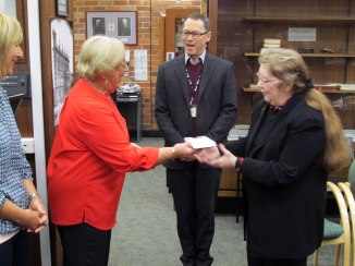 Mrs Pat Wilson (in red) with daughter Amanda, presenting the book to Lyn Keily and Mark Sutherland (centre). Photo: Gregg Heathcote