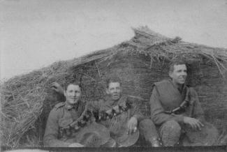 Bob Johnston, Alf Killick and William Dalton sitting at the end of a haystack during World War 1